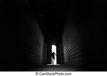 Person's silhouette entering the backlit hall
