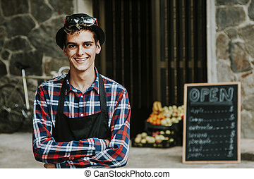 enterprising man smiling in front of business