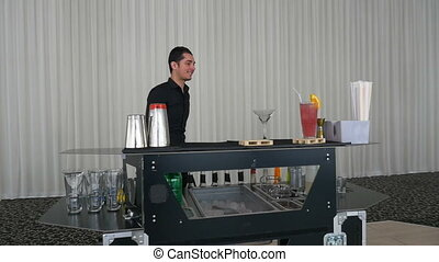 Entertainer making flair bartending moves with shaker at a bar in slow motion