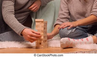 couple playing block-stacking game at home - entertainment...