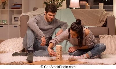 happy couple playing block-stacking game at home -...