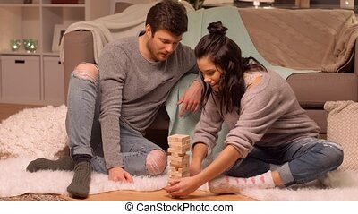happy couple playing block-stacking game at home