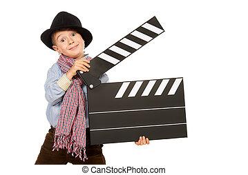 entertainment - Cheerful boy holding clapper board....
