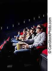 Entertainment - Young smiling people watch movies in cinema