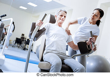 Enthusiastic baby boomer using weight machine in a rehabilitation center