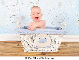 enthusiastic baby boy in blue wicker basket