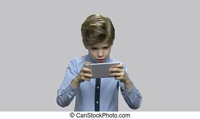 Enthusiastic boy using smartphone with victory expression....