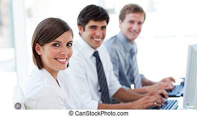 Enthusiastic business people working at computers in the...