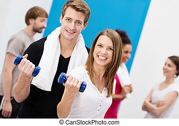 Enthusiastic couple working out with dumbbells