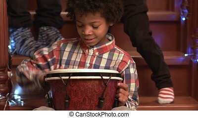 Enthusiastic darkskinned boy playing drum.