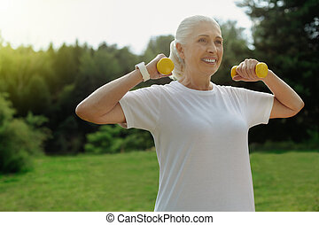 Enthusiastic elderly lady exercising with weights