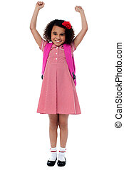 Enthusiastic elementary school girl posing with arms raised ...
