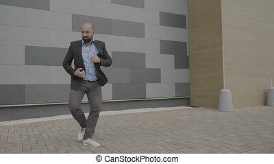 Enthusiastic employee man feeling empowered dancing in...