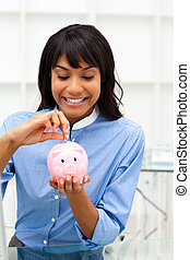 Enthusiastic ethnic businesswoman saving money in a piggybank in the office
