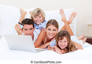Enthusiastic family buying online lying down on bed at home