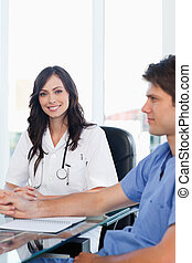 Enthusiastic female doctor sitting at the desk while looking at the camera near a co-worker