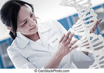 Enthusiastic female researcher examining dna model -...