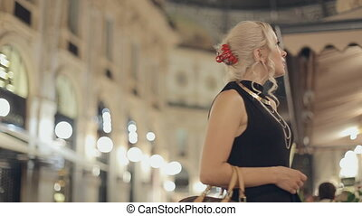Enthusiastic girl in downtown of Milan at night