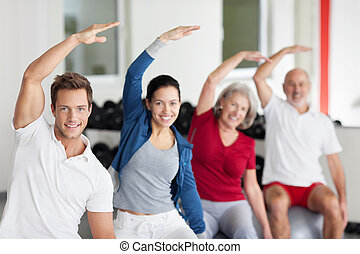 Enthusiastic group doing aerobics at a gym