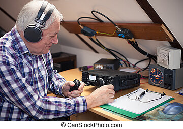 Enthusiastic middle-aged radio-amateur at his workplace