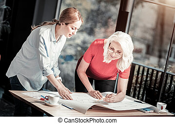 Enthusiastic senior woman helping her younger colleague