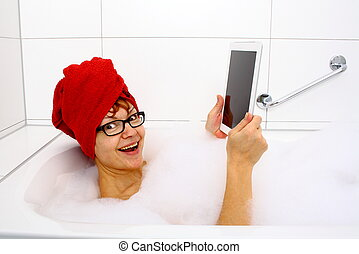Enthusiastic woman in bathtub with tablet