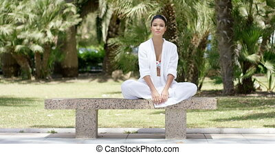 Enthusiastic woman sitting on granite bench