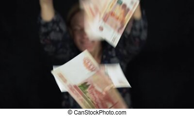 Enthusiastic woman throws banknotes five thousand rubles on...