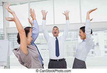 Enthusiastic work team cheering together