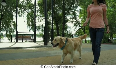 Enthusiastic young woman walking with her dog