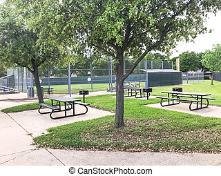 Entire baseball field with chain link fence is empty in Dallas, Texas, America. Vacant picnic tables and bleachers in closed community sport facility as Coronavirus covid-19 pandemic outbreak