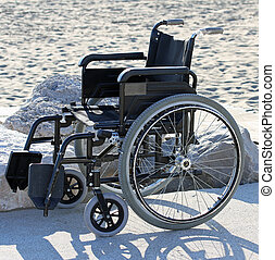 wheelchair on the sandy beach by the sea in summer