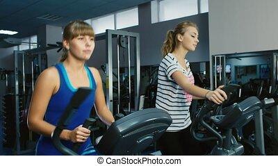entraîneur, gymnase, deux, séduisant, entraîné, elliptique, femmes