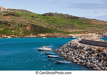 Entrance in bay, seafront with lighthouse on seafront. Gozo island, Malta.