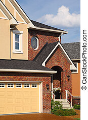Entrance in new two-storied brown brick cottage with beige garage.