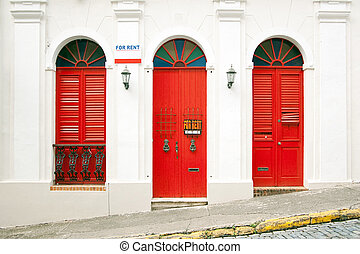 "Entrance of a classic styled aparment with vintage tall red windows and marks ""FOR RENT"""