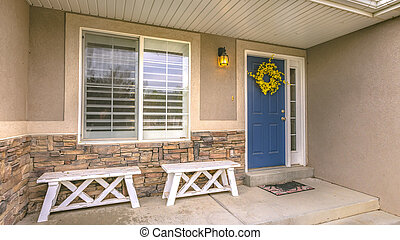 Entrance of a home with porch and blue front door
