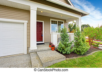 Entrance porch with railings and red door. Front yard landscape with decorative fir trees
