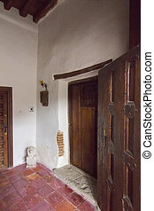 Entrance to an old stone house with wooden doors and white walls