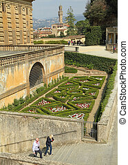 entrance to the Boboli Gardens in Florence with view of  flowerbed maze and  the Palazzo Vecchio ( Old Palace )at the background , Unesco World Heritage site, Italy