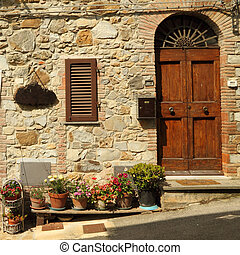 entrance to the tuscan villa with many flowerpots on the...