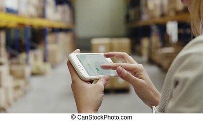 entrepôt, femme, ouvrier, smartphone.