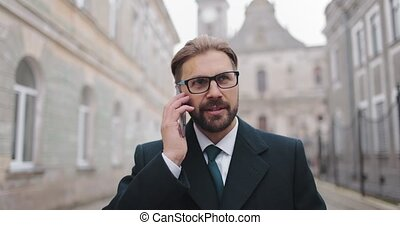 Confident bearded entrepreneur in eyewear talking on mobile and walking on street. Mature man in formal clothing having working conversation at city center.