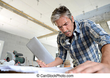Entrepreneur in house under construction checking plan