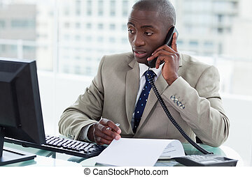Entrepreneur making a phone call while looking at his...