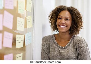 Entrepreneur smiling in front of her task cards