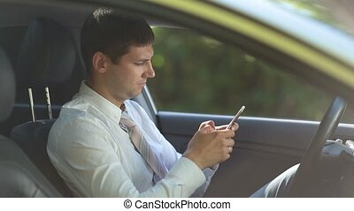 Entrepreneur surfing net on phone in car - Side view of...