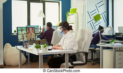 Entrepreneur wearing face mask against coronavirus discussing on video meeting using headset with business partner in new normal financial office. Multiethnic coworkers respecting social distance.