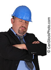 Entrepreneur with hardhat falling asleep
