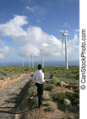Entrepreneur with laptop observing wind turbines